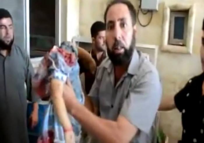 A distraught Syrian Christian holds up the body of his child, beheaded by Islamic State.